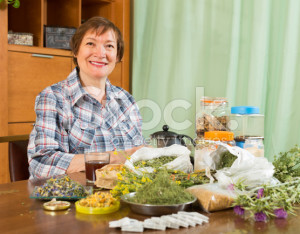 stock-photo-45105572-mature-woman-with-herbs-at-table